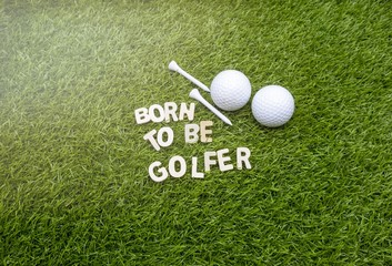 Born to be golfer with golf ball and tee on green