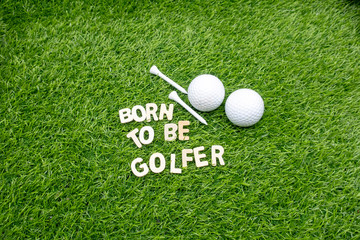 Golf born to be golfer with golf ball and tee on green