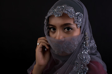 Portrait of muslim woman looking at camera over black background.