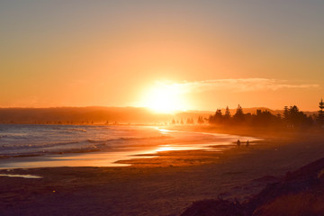Two people walk the beach as the huge orange sun sets in the background in Gisborne, New Zealand.
