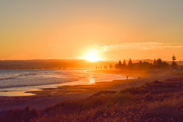 Couple walk along the empty beach at sunset in Gisborne, New Zealand. Wall mural