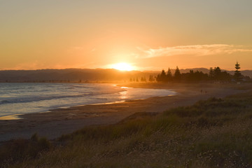 The bright sun sets on a quiet beach in Gisborne, New Zealand.