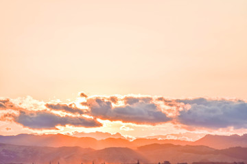 A pale peach colored and calm sunset floats above the countryside in Gisborne, New Zealand.