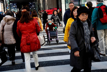 A woman uses a walking aid as she crosses the street at a crosswalk in Tokyo