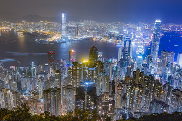 Hong Kong skyline at night as seen from Victoria Peak. Illuminated skyscrapers in foreground, Hong Kong harbor in background.