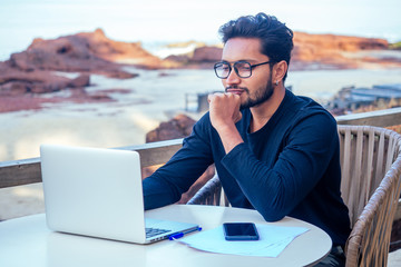 freelancing and remote work.handsome male student working laptop keyboard sitting in cafe on the beach with free internet.Young indian man using computer in summer vacation by the sea Wall mural