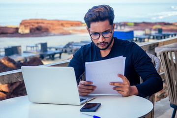 handsome and young successful indian man freelancing surfing remote work with a laptop on the beach by the ocean.india businessman freelance programming online copywriter paradise landscape dream job