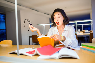 Surprised Woman reading Book in library