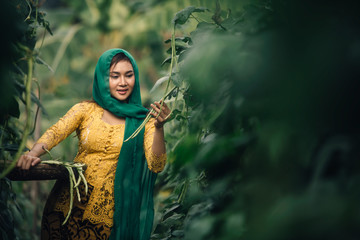 Asian woman in bali costume Indonesian national dress Collect beans in her vegetable garden.