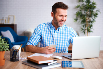 Fototapeta Smiling man working with laptop