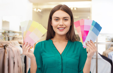 fashion, style and shopping concept - smiling young woman with color swatches or samples over...