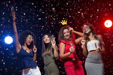 Happy women celebrating New Year at nightclub
