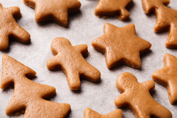 Raw gingerbread cookies. Christmas figures from dough on paper