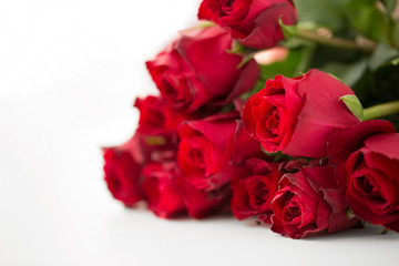flowers, valentines day and holidays concept - close up of red roses bunch