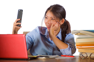 young beautiful and happy Asian Chinese student girl studying with book pile and laptop computer desk taking selfie picture with mobile phone smiling cheerful isolated