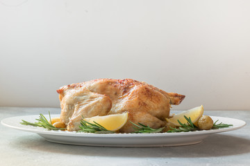 Roasted chicken with potatoes and rosemary on white table. Copy space.