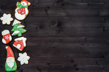 Tasty homemade gingerbread cookies with icing on dark wooden table, top view, flat lay. Christmas background with boder of santa, snowman, snowflake, stocking, fir tree, mitten and house, copy space