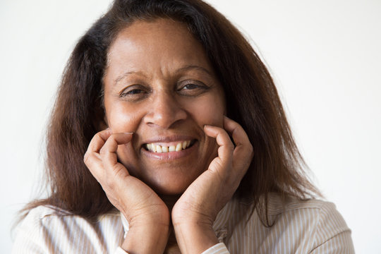 Cheerful mix raced lady smiling at camera. Closeup of smiling middle aged woman leaning chin on hands. Happy face expression concept