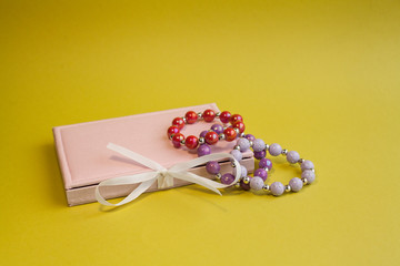 bracelets and pink gift box on yellow background