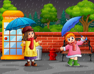 Cartoon two girl carrying umbrella under the rain in the city park