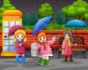 Cartoon three girl carrying umbrella under the rain in the city park