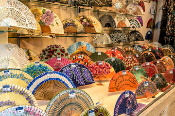 Display of colorful Spanish hand fans in downtown Seville, Andalusia, Spain; selective focus.