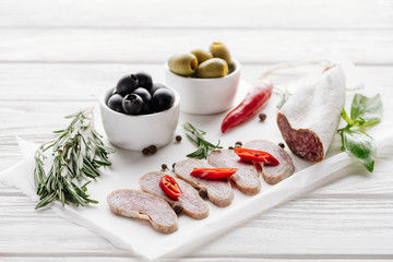 close up view of meat appetizers with olives, rosemary and basil leaves on white wooden tabletop
