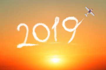 Plane flies leaving a trail 2019 of clouds in the sunset sky. Happy New year concept travel