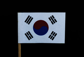 A unique flag of South Korea on toothpick on black background. A white field with a red and blue taegeuk in the center that is surrounded by four varying groups of short black bars toward each corner