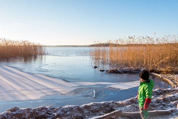 Young child in winter clothing looking at a beautiful cold sunny scenic tranquil winter landscape of ice, water and reed against a clear blue sky.