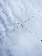 Electrical wires in the air in the shape of X against cloudy sky.