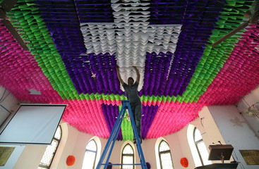 A man decorates the ceiling of a church ahead of Christmas celebrations in Ahmedabad