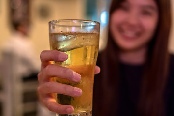 Asian young woman in happiness action and drinking beer in pub and restaurant with low light place, relax and drink concept
