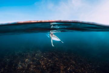Foto op Plexiglas Zalm Surfer woman relax and sit at surfboard. Surf girl in blue ocean.