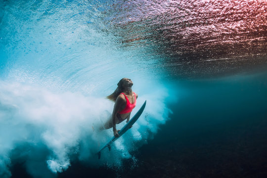 Sporty surfer woman dive underwater with under barrel wave.