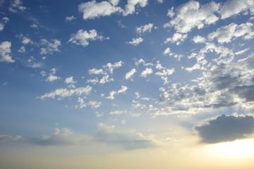 Sonnenaufgang, Sonnenstrahlen und Wolken am blauen Himmel über dem Meer