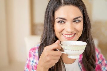 Smiling beautiful brunette drinks a cup of tea.