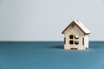Real estate concept. Small toy wooden house with keys on grey background