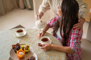 Senior woman pours tea from teapot into her daughter's cup