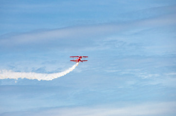 red airplane doing acrobatics in blue sky