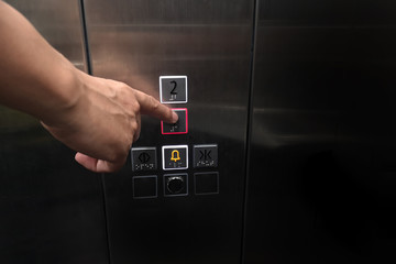 Men's hand with the press of control buttons interior elevator have braille panel for the disabled and empty space for text.