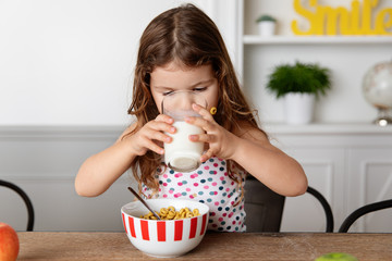 Little girl drinking milk at kitchen table