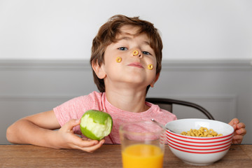 Goofy little boy with cereal stuck on face at kitchen table