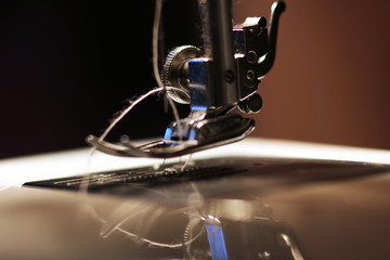 The woman works on the sewing machine. Clothes manufacture.