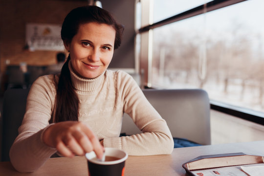 The woman has a rest in cafe, sits at a table with a cup of tea