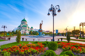 Beautiful colorful square in front of the Christian church in the city center during sunset with blue yellow sky. Monument to Saint Vladimir the Baptist and Vladimir Cathedral, Astrakhan, Russia.