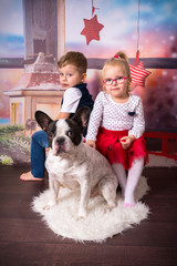 Boy and girl twins posing with the dog in christmas scenery