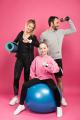 athletic family posing with fit ball, fitness mat and dumbbell while kid showing thumb up, isolated on pink