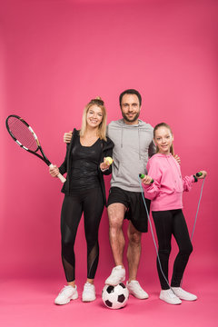 sporty family with sport equipment on pink