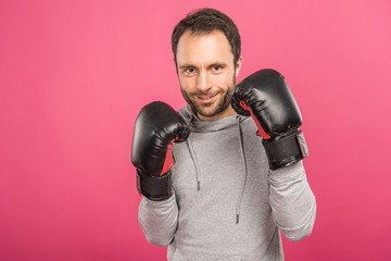 handsome smiling boxer posing in box gloves, isolated on pink